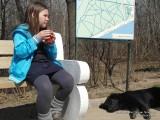 Девочка пьет чай на скамейке в парке рядом спит собака