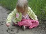 Фото девочка рисует на песке