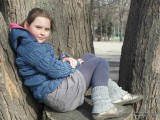 Фото девочки, сидящей на пеньке в парке