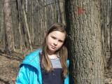Девочка у дерева в весеннем лесу фото