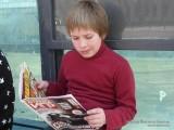 Мальчик читает игровой журнал на троллейбусной остановке фото