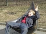 Мальчик развалился в кресле-скульптуре в парке Музеон на Крымской набережной