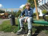 Фото мальчик на роликах сидит на скамейке