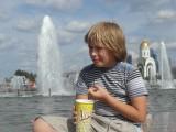 Мальчик есть попкорн у фонтана