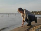 Девушка рисует пальцем на песке