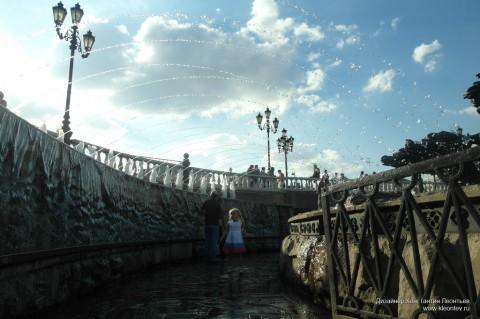 Девочка под струями фонтана